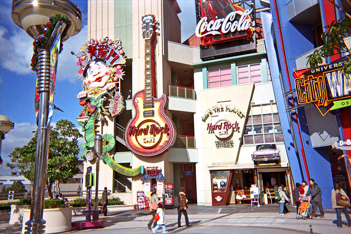The Hard Rock Cafe Osaka Universal Studios featuring a giant neon guitar and a massive neon Japanese kite out front.