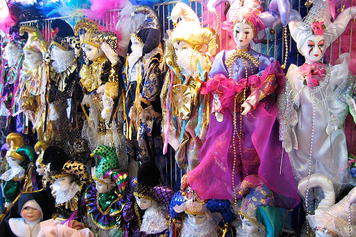 Colorful New Orleans dolls and puppets with mime faces and shiny fabric clothes.