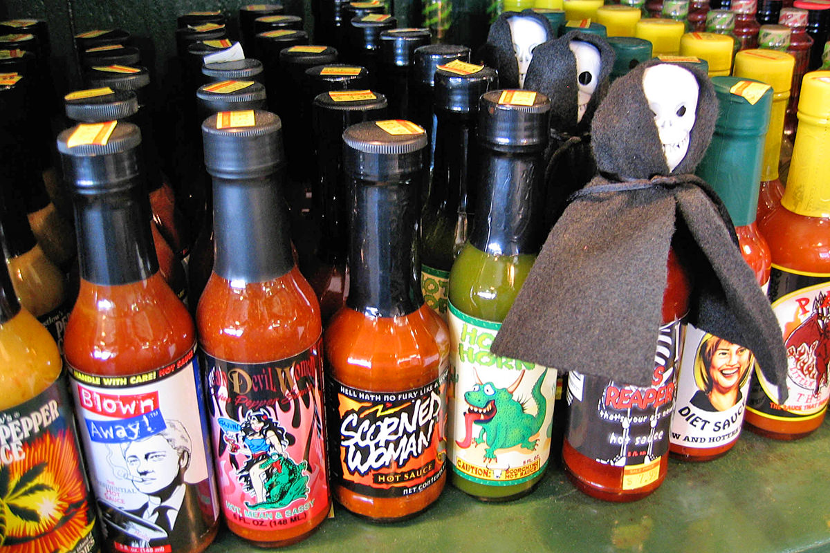 A shelf filled with different hot sauces with clever names like SCORNED WOMAN.