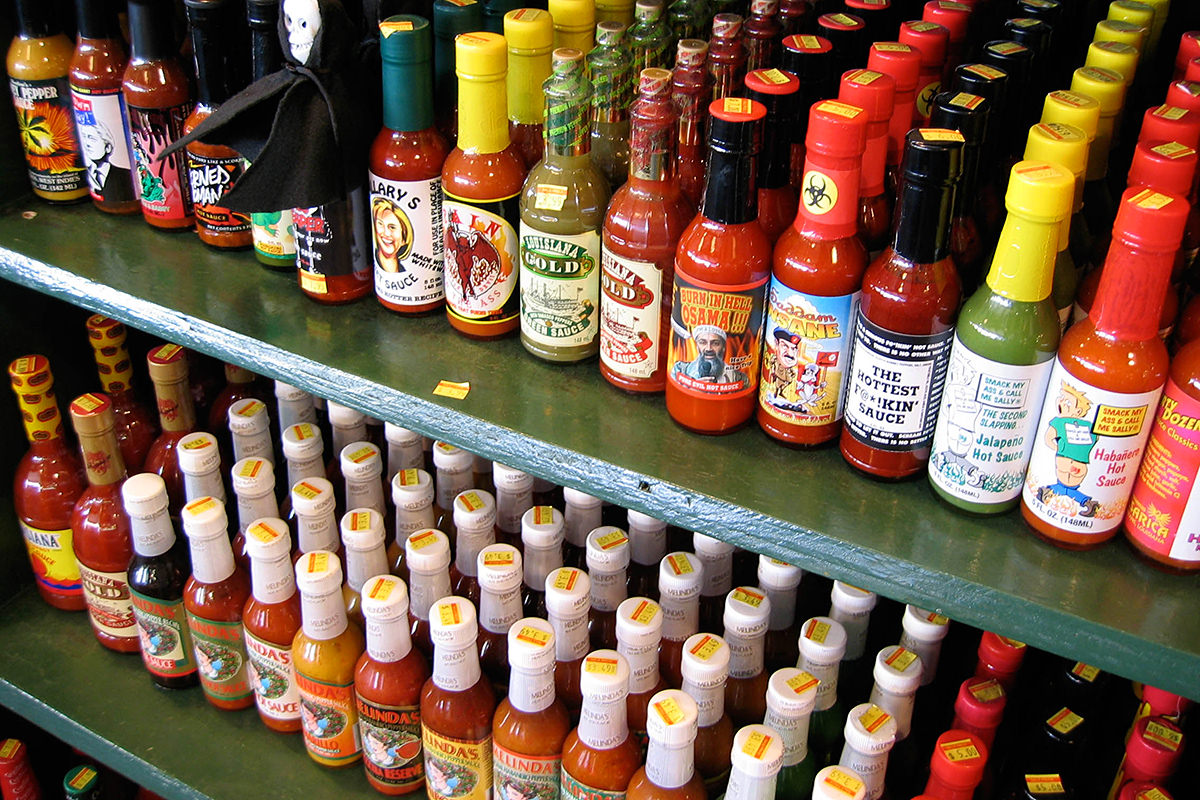 Shelves filled with many, many different hot sauces.