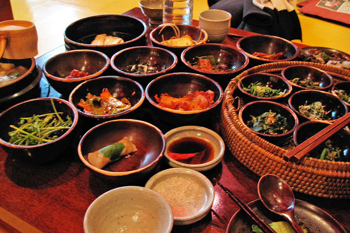 A low table filled with all kinds of small dishes filled with various Korean foods.