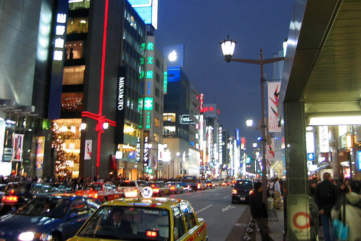 Looking down The Ginza at night with all the buildings lit up and a lighted Apple logo on top of the Apple Store Tokyo.
