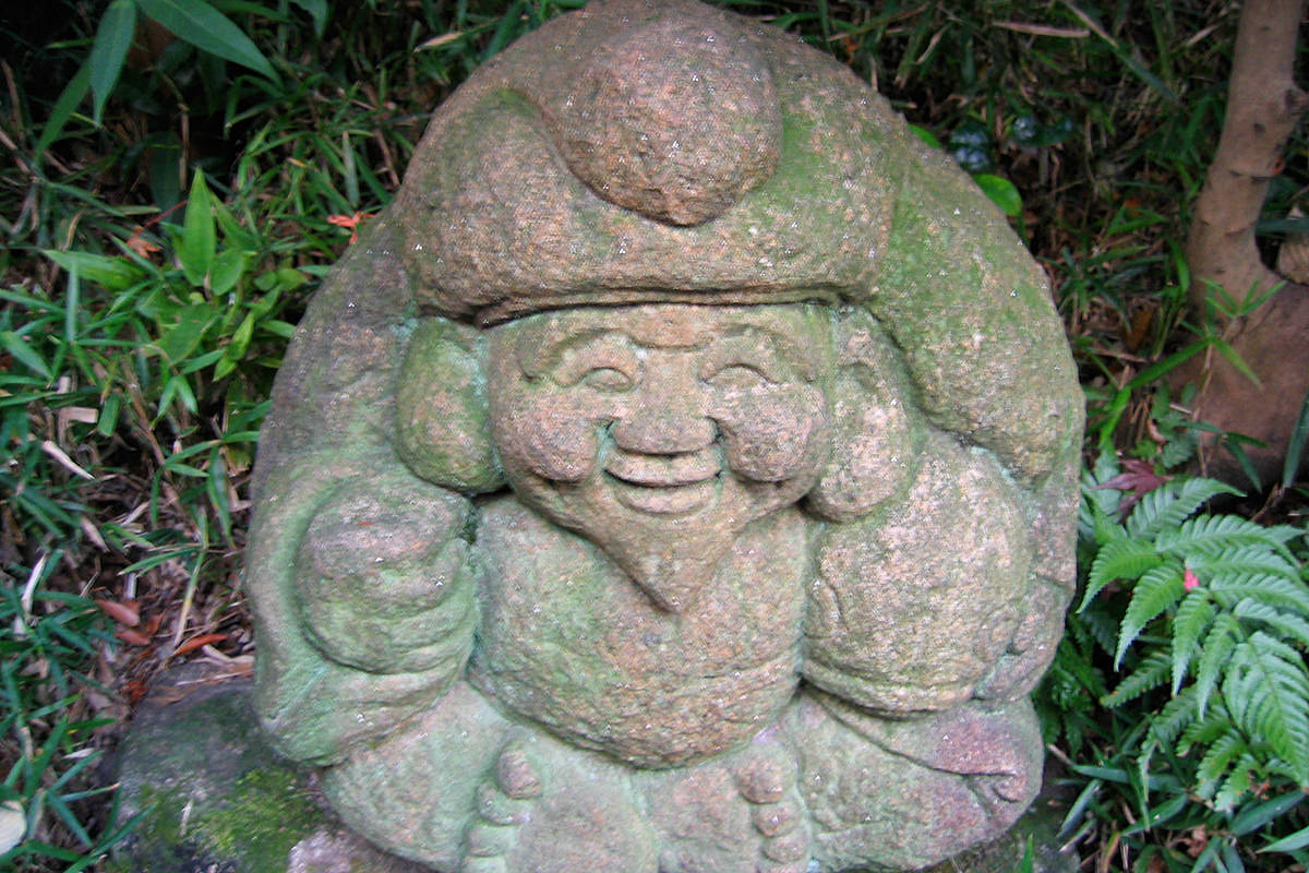 A stone carving of a smiling Buddha in a park at Chinzan-so.