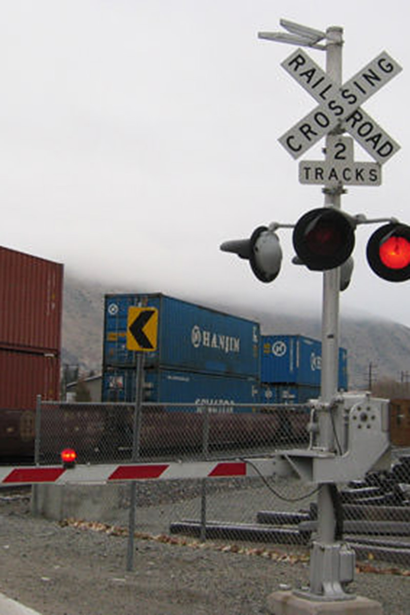 A railroad crossing on a cloudy winter day with the cross arm down to block traffic and a train passing behind it.