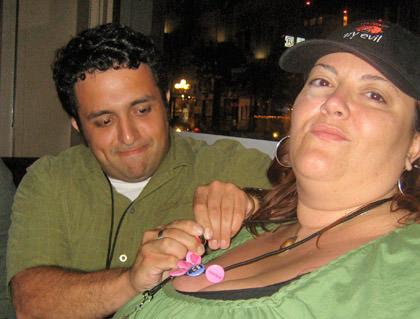 Vahid attempting to attach button flair on Hilly's lanyard