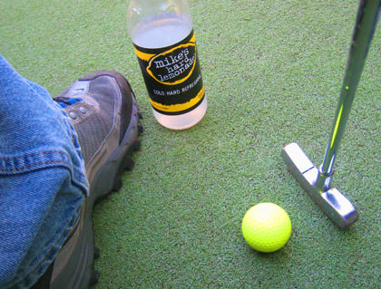 My foot. A golf club. A golf ball.A Mike's Hard Lemonade.