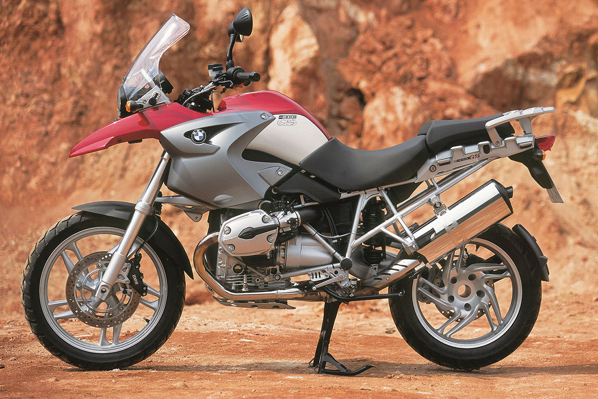 The new BMW R1200 GS parked in a dessert setting in front of some pretty red rocks.