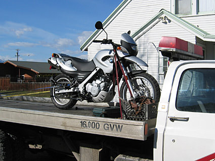 My motorcycle strapped to the bed of a tow truck.
