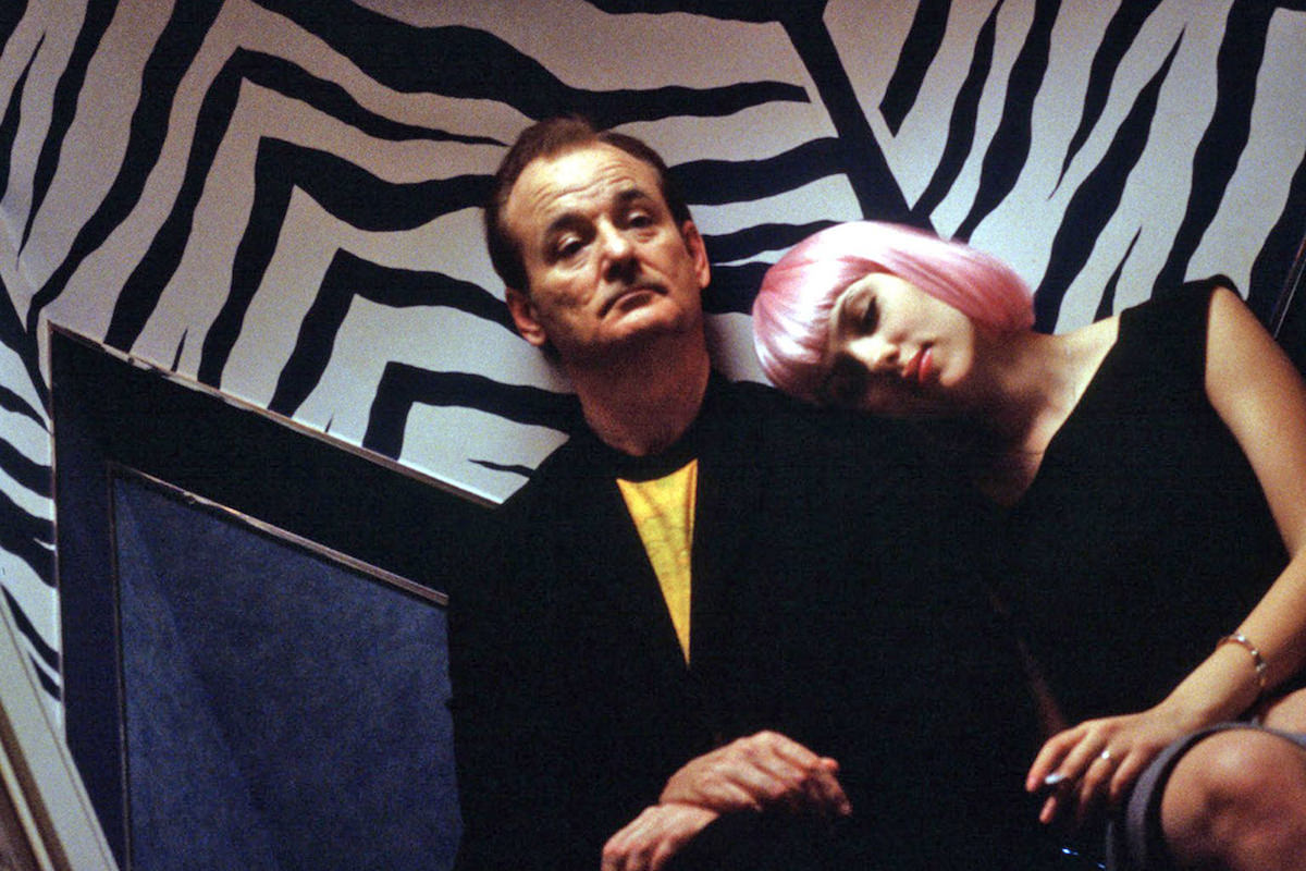 Bill Murray and Scarlett Johansson in a scene from Lost in Translation where they are sitting against a zebra-stripe wall looking tired.