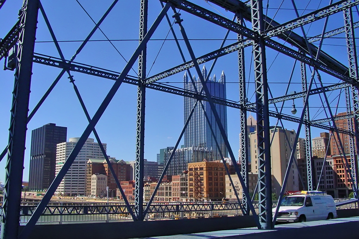 A view from a large metal bridge looking towards downtime Pittsburgh and some beautiful buildings.