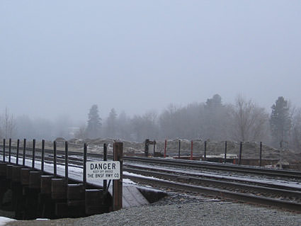 A fence with a DANGER! sign bordering some railroad tracks on a foggy day.