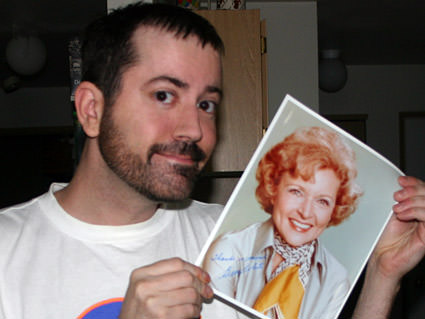 Me holding an autographed photo of Betty White.