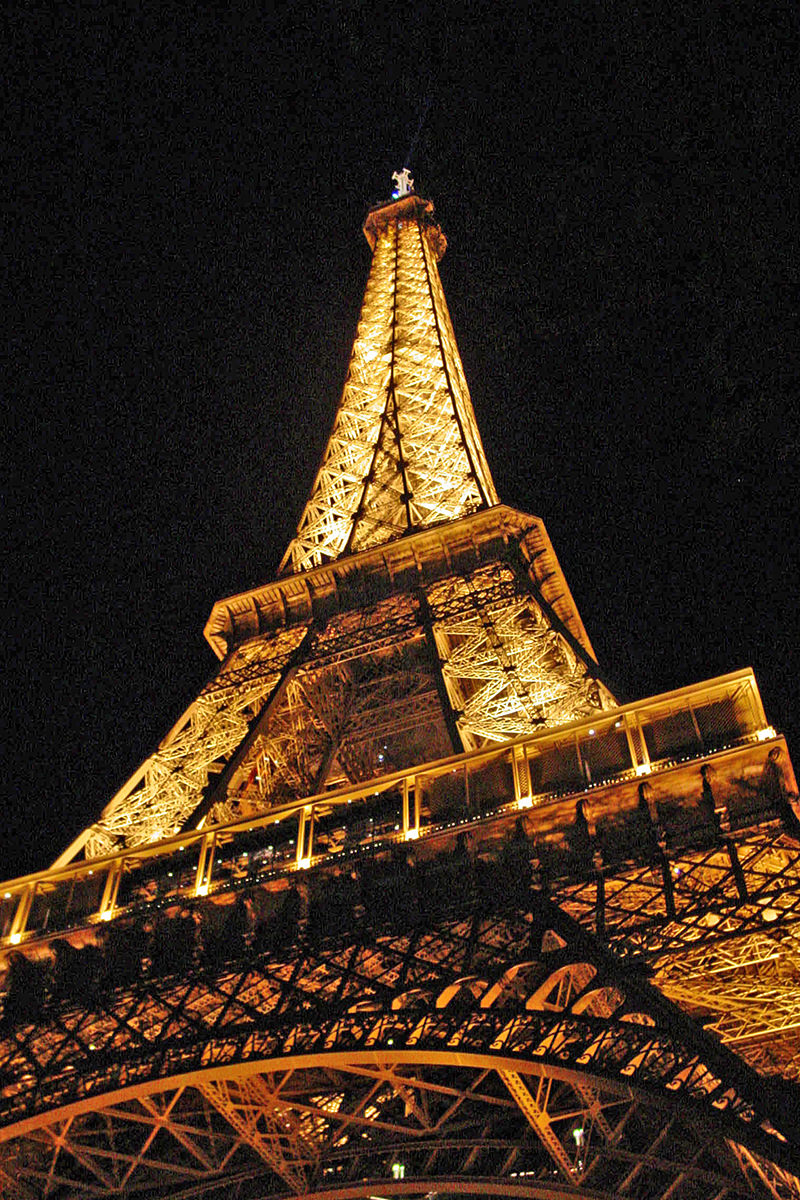 The Eiffel Tower lit up in yellow light at night.