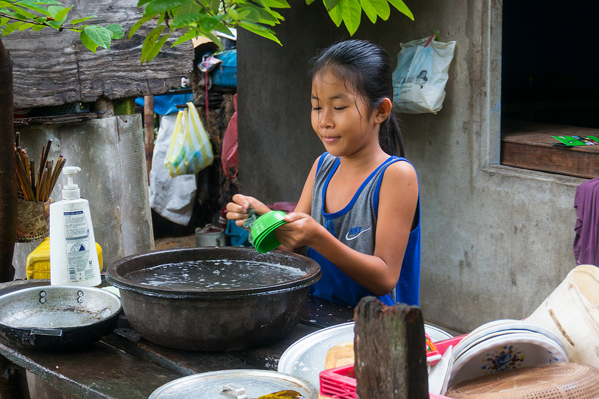 Girl Washing Dishes in Hoi An, Vietnam