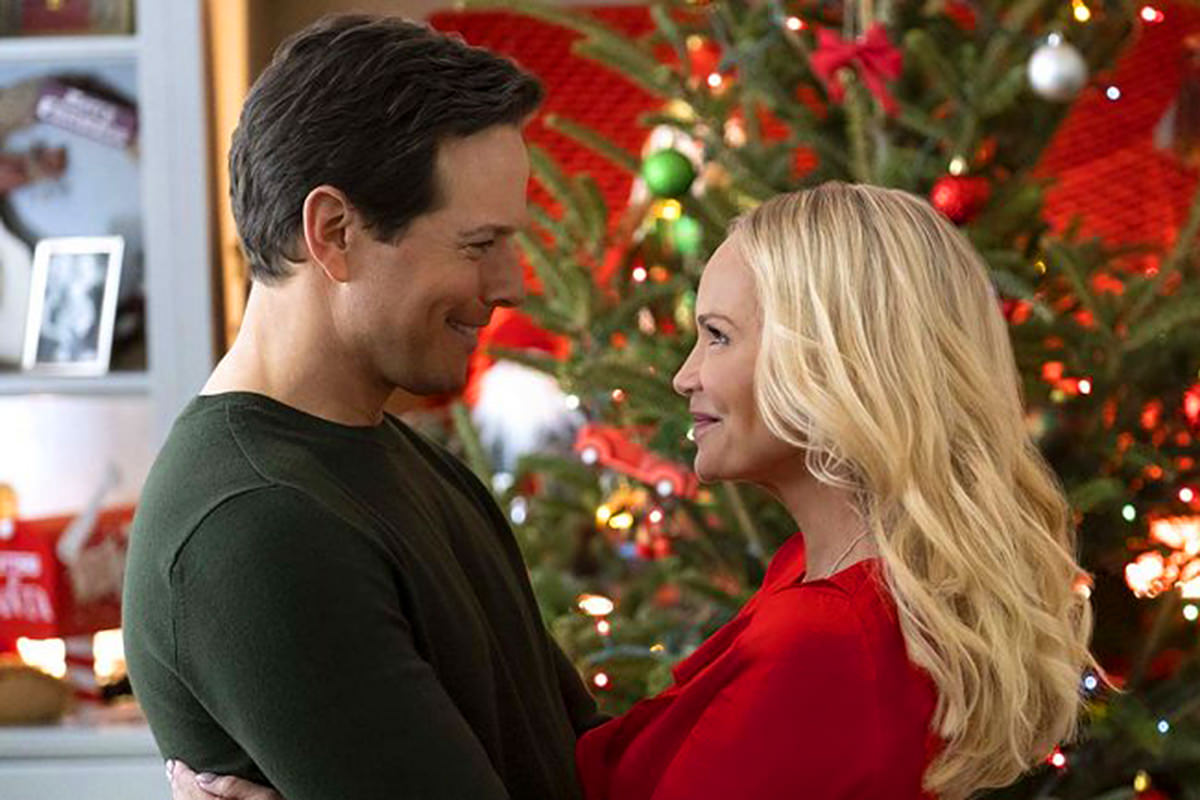 Kristin Chenoweth and Scott Wolf staring into each other's eyes in front of a Christmas tree.