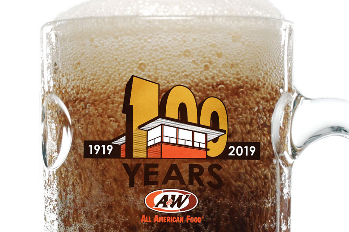 A mug of frosty A&W root beer with a 1919-2019 logo on it, showing a giant '100' that's cut into an outline of an A&W drive-in.