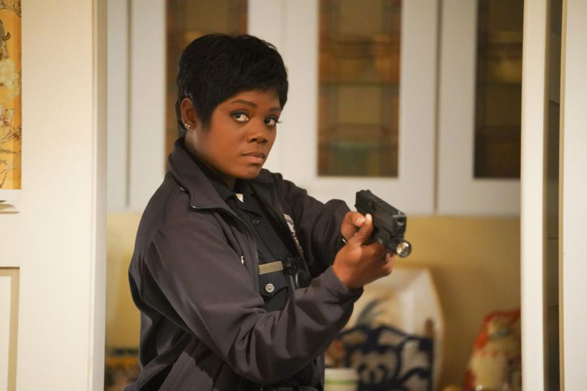 Afton Williamson as police officer Talia Bishop on The Rookie holding a gun and about to kick ass.
