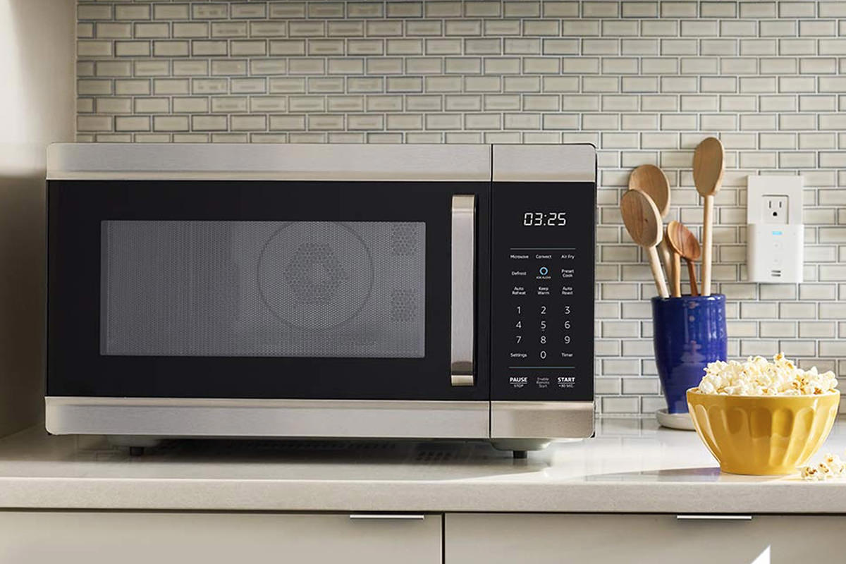 An Amazon Oven, looking much like a microwave, sitting on a kitchen counter next to a bowl of popcorn.