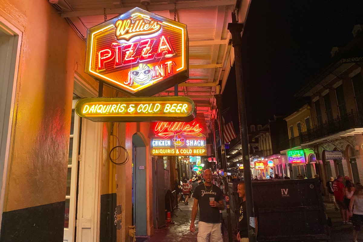 The glowing neon sign for Willie's Pizza with a glowing Willie's Chicken sign behind it.