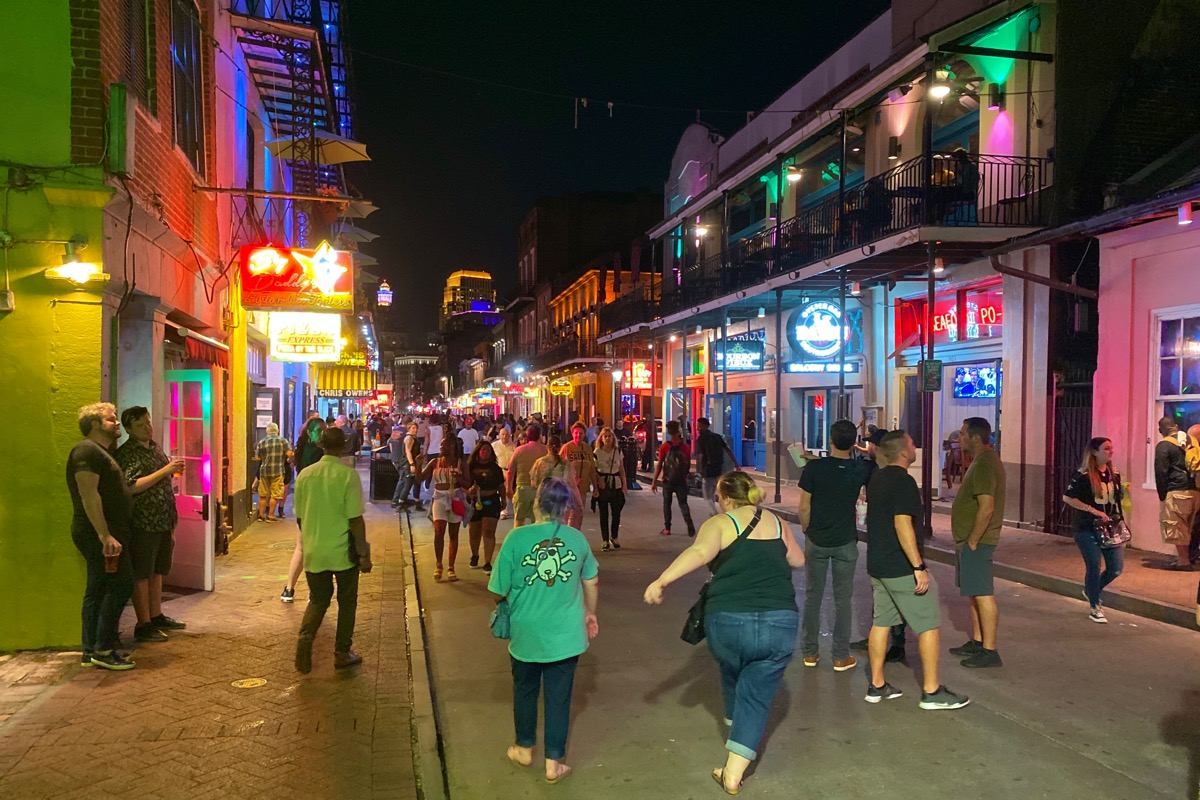 A woman about to fall on her drunk ass as she embraces the madness of Bourbon Street at night.