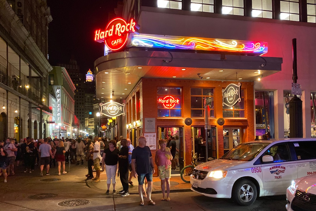 The Hard Rock Cafe New Orleans, all aglow in neon lights as people walk by.