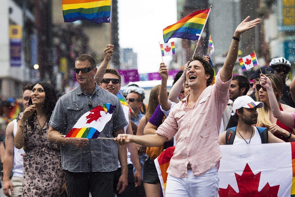 Prime Minister Justin Trudeau marching in a Pride parade with rainbow flags, fun, and confetti.
