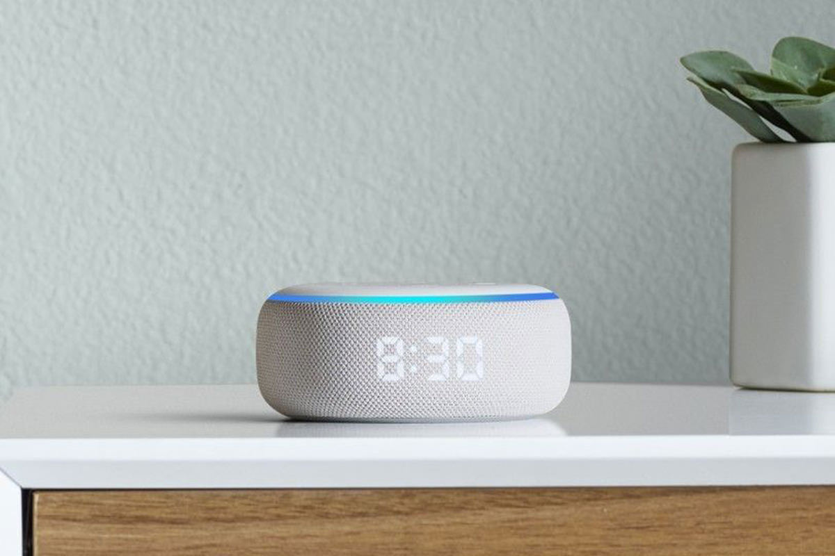 An Echo Dot sitting on a corner table with the time serenely glowing through the fabric of the speaker cover the circles the hockey-puck-shaped device.