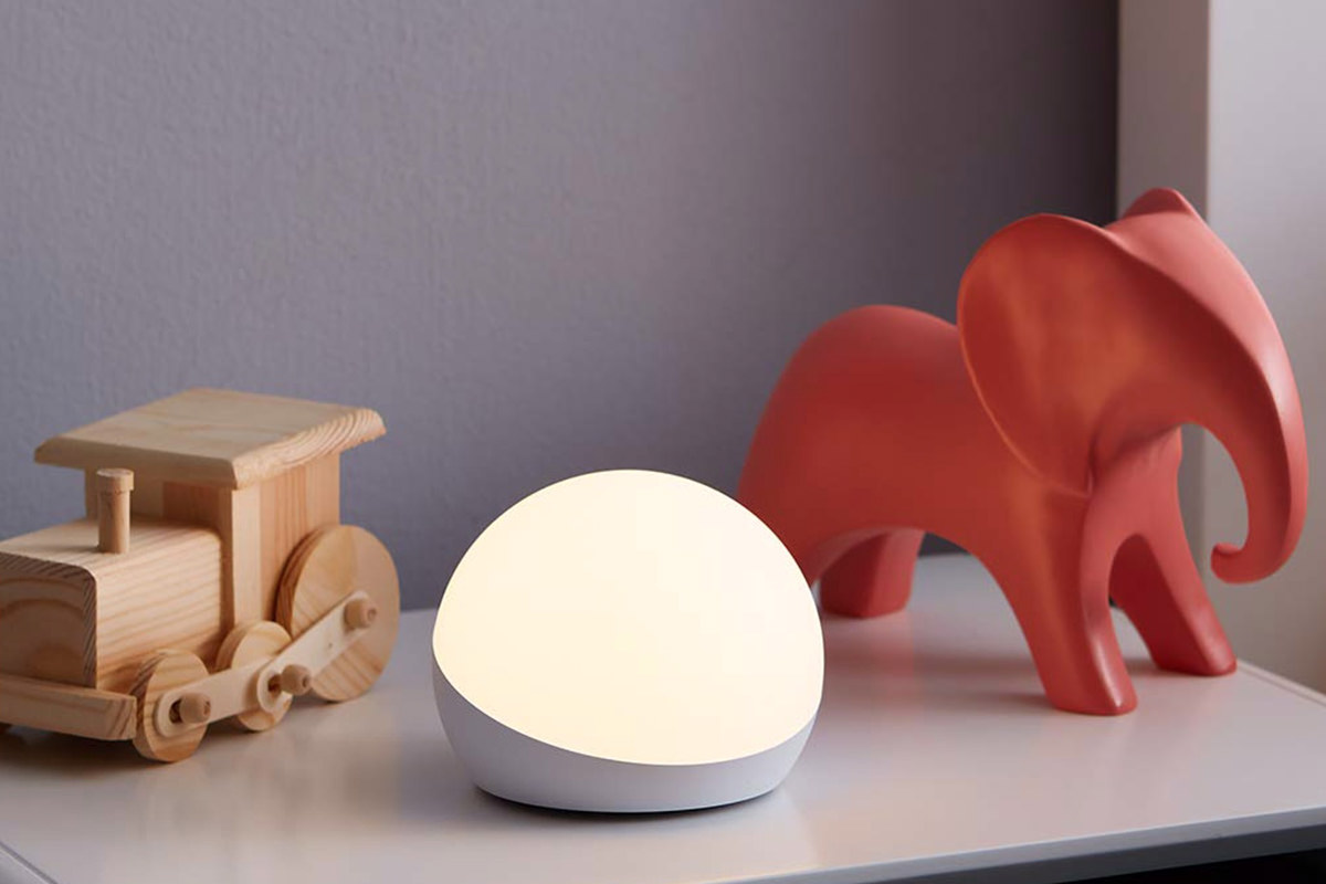 A glowing orb light sitting on a child's dresser with wooden toys around it.