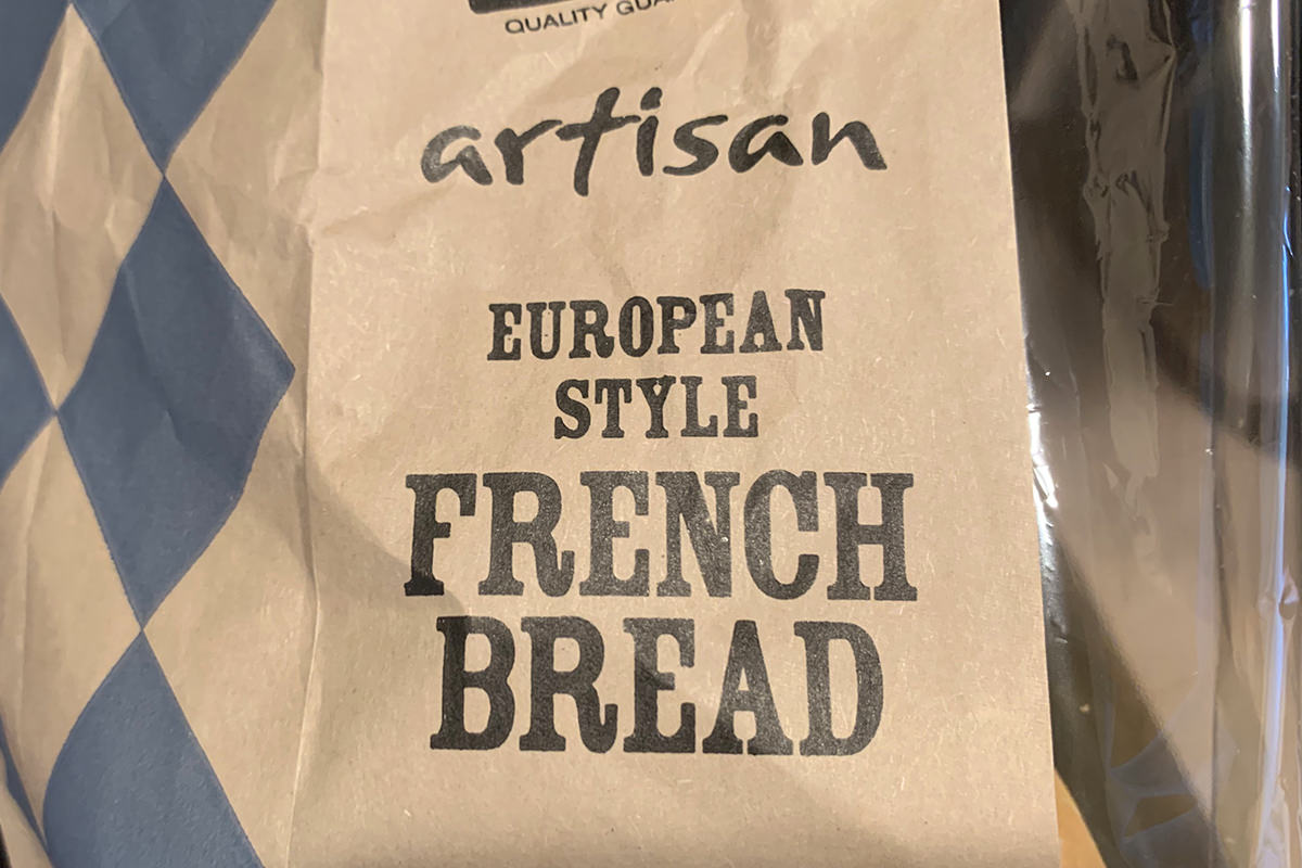 A brown bag wrapped which says Artisan European Style French Bread on it.