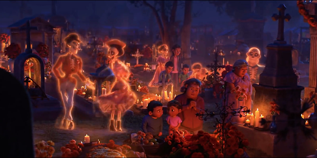 A frame from the animated masterpiece COCO from Disney Pixar showing skeletal spirits visiting a decorated cemetery while people are praying at a gravesite in the foreground.