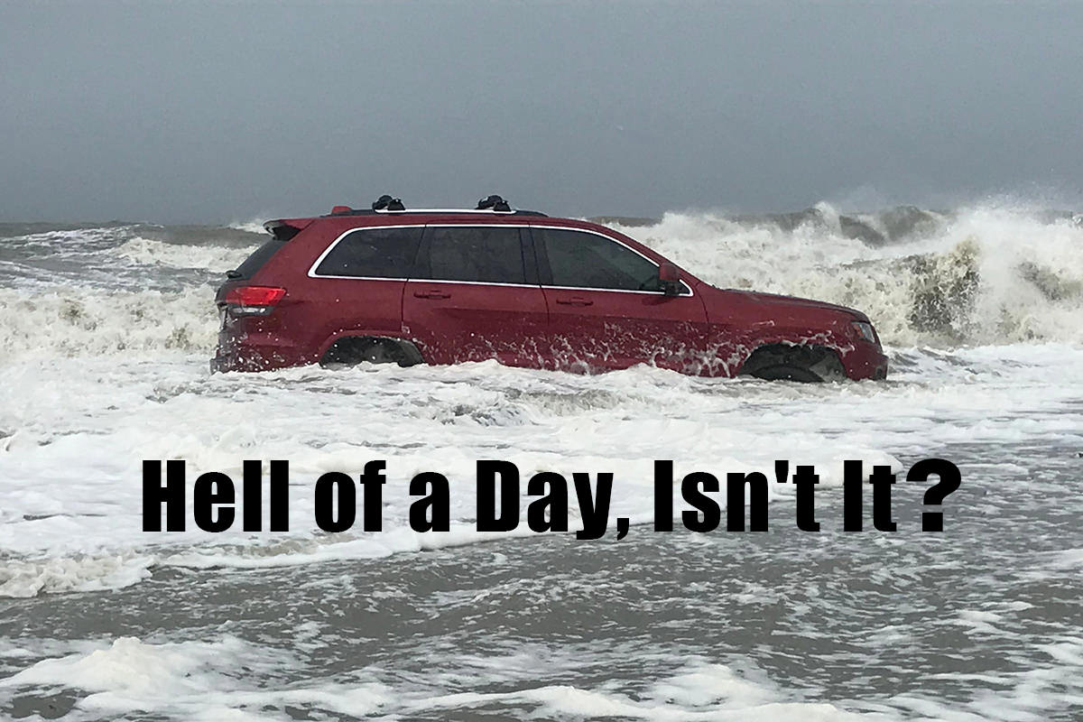A photo of a red SUV stuck on the beach while waves crash around it... and I've added the text HELL OF A DAY, ISN'T IT? to the bottom.