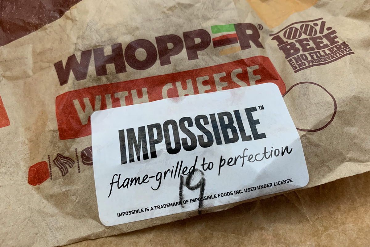 A Burger King Whopper hamburger in a wrapper with an Impossible Whopper sticker on the front.