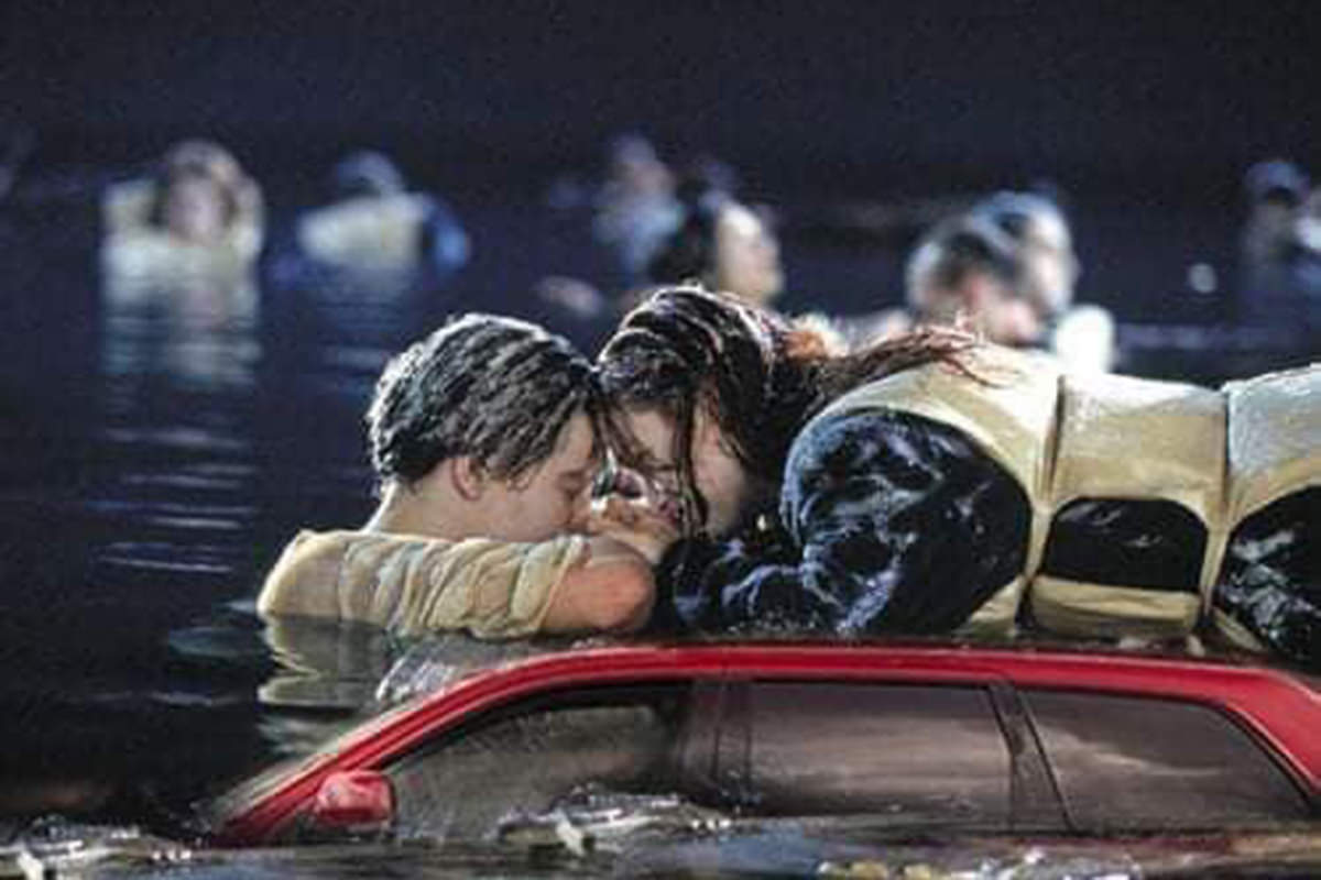 Rose and Jack from Titanic on top of the beached car which is now sinking into the North Atlantic Ocean.