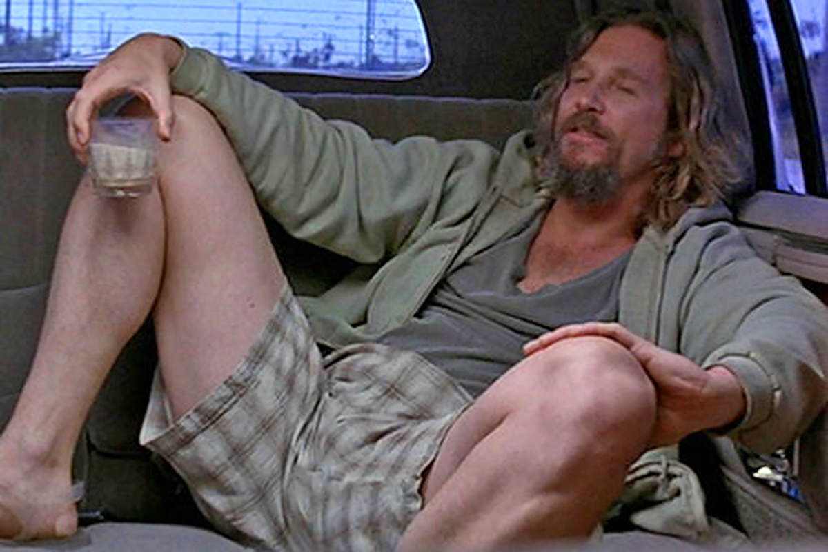 Jeff Bridges as The Dude from The Big Lebowski, sitting spread eagle in a limo while drinking a white Russian.