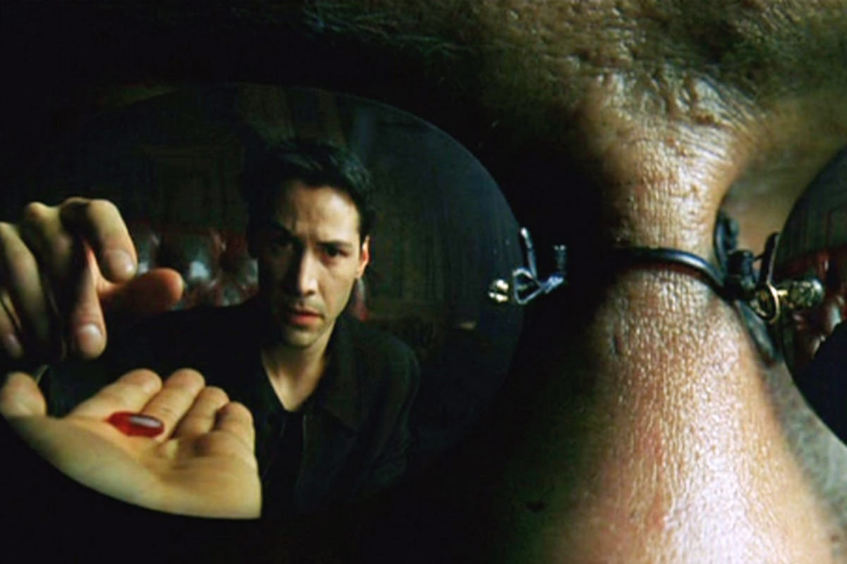 Neo is reflected in Morpheus' glasses taking the red pill in a scene from The Matrix.