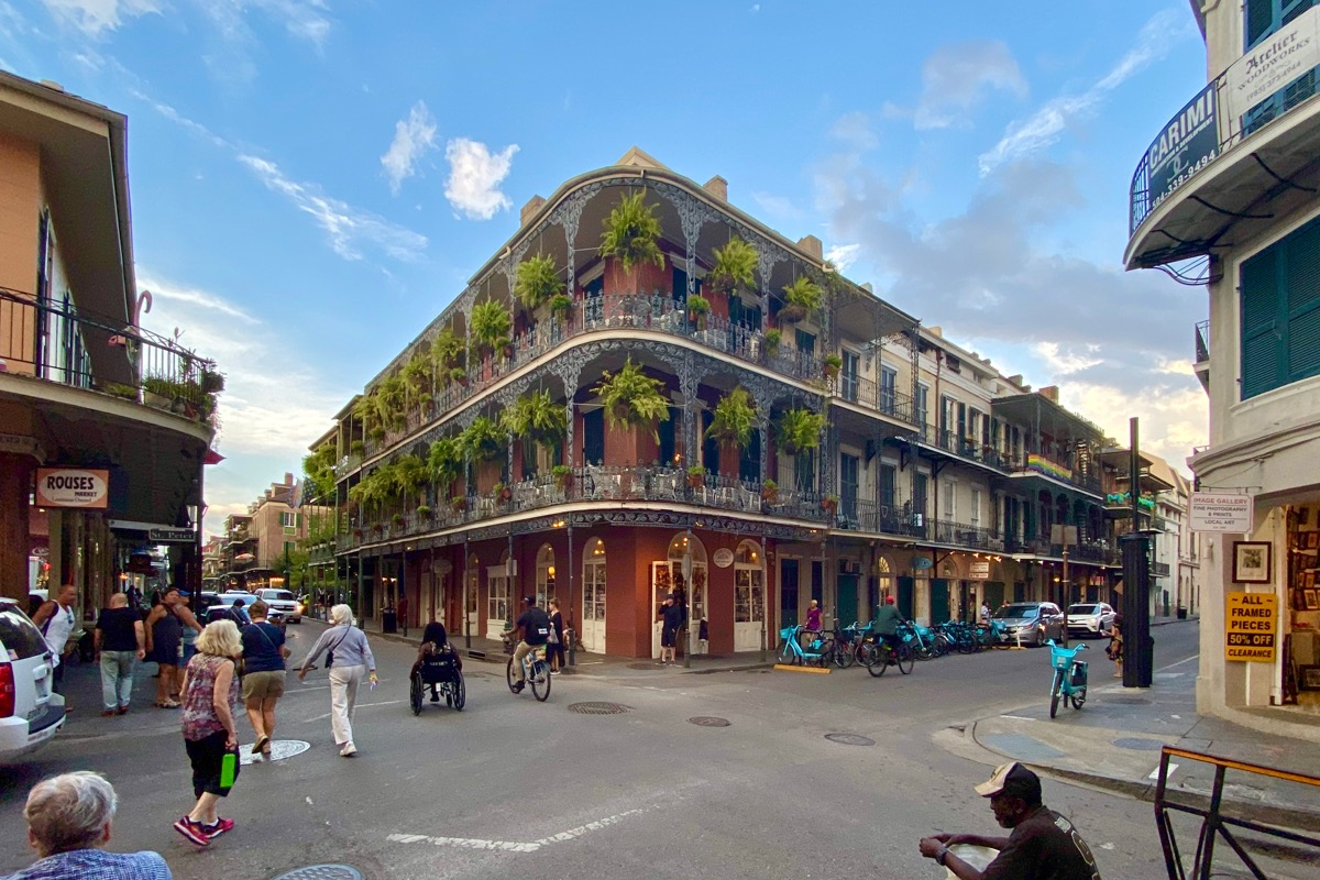 This time a wide-angle photo of a beautiful New Orleans building with wrought iron railings and massive ferns hanging on the balconies... with people in the street in front of and around it.