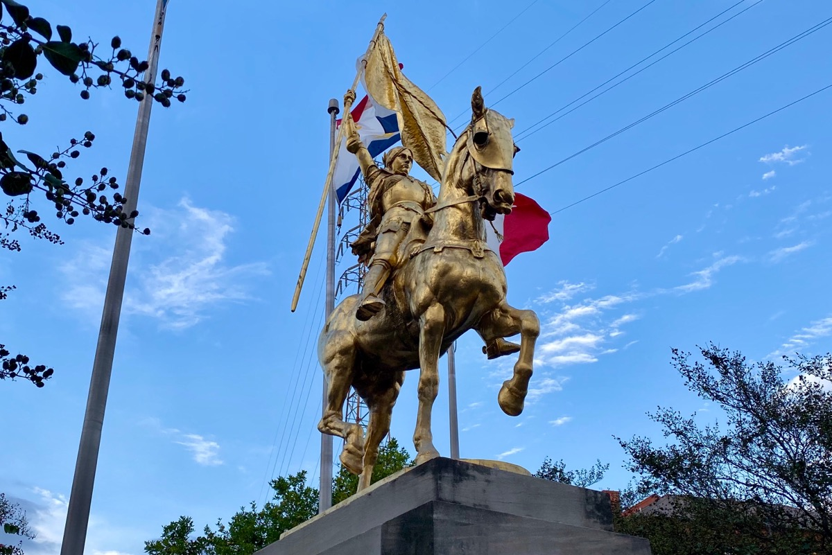 A beautiful gold-covered statue of Joan of Arc, which was a gift to New Orleans from the people of France. A French flag can be seen on a pole behind it.