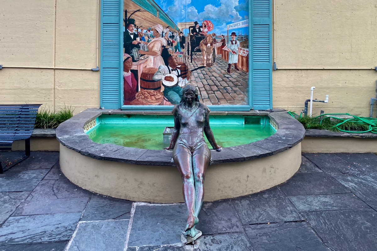 Statue of a woman in brass sitting on the edge of a fountain with a painting of New Orleans behind it.