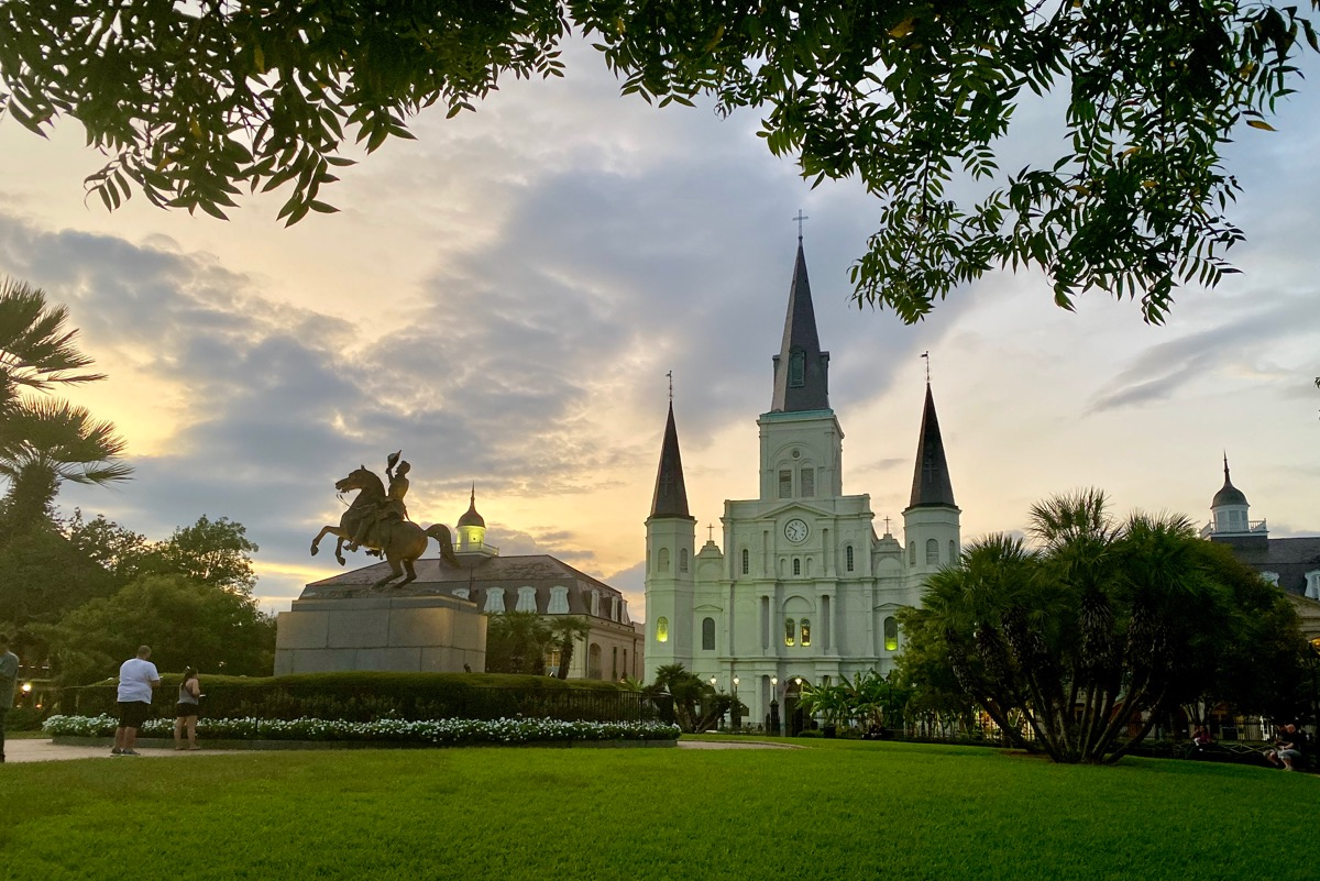 St. Louis Cathedral at dusk sitting behind Jackson Square with beautiful green lawns and a statue of Jackson on a horse in the middle.