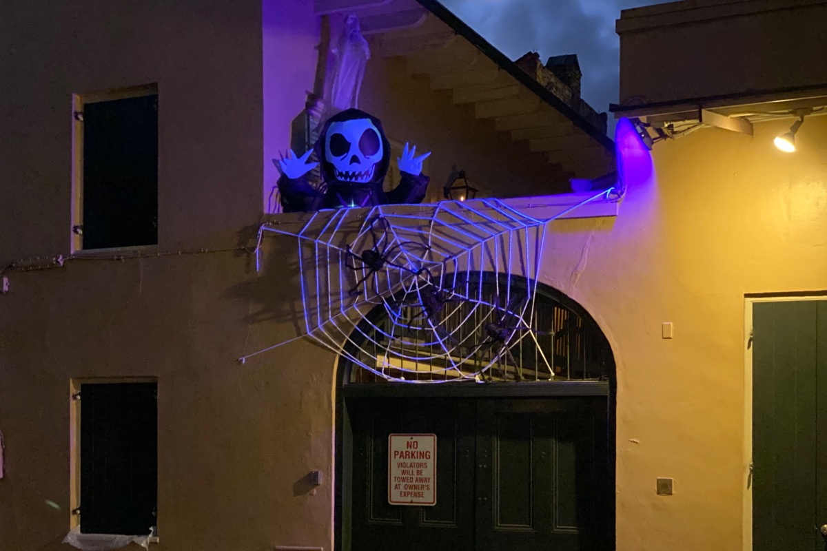A yellow building with a spooky purple glow coming from the balcony where a skeleton monster is peeking out and there's a spider in a giant web hanging over.
