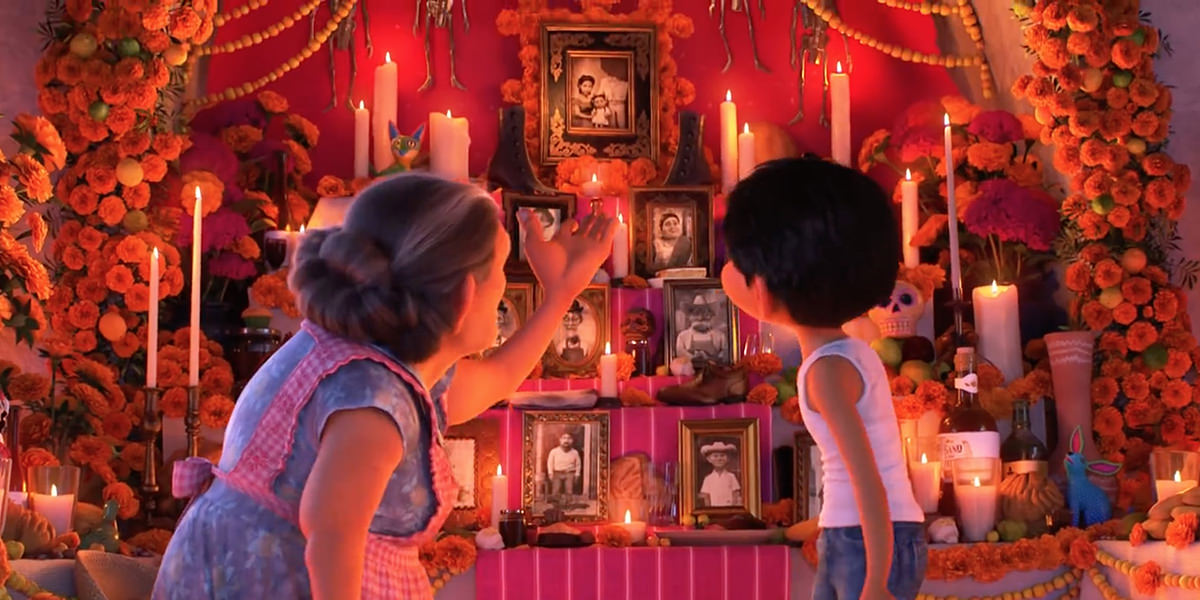 A frame from the animated masterpiece COCO from Disney Pixar showing a colorful altar decorated with marigold flowers, candles, and photos of the dead while a grandmother is explaining it to her grandson Miguel.