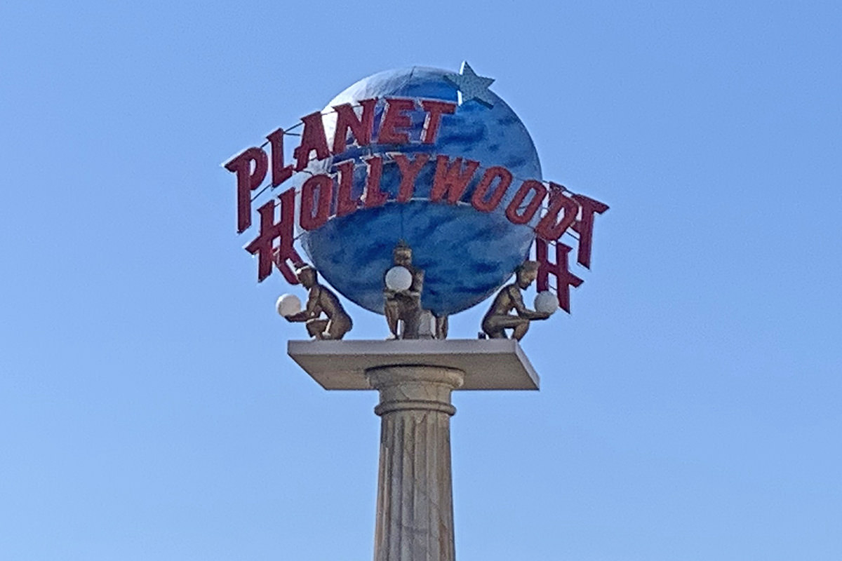 A Planet Hollywood sign at Caesar's Palace against a flawless blue sky.