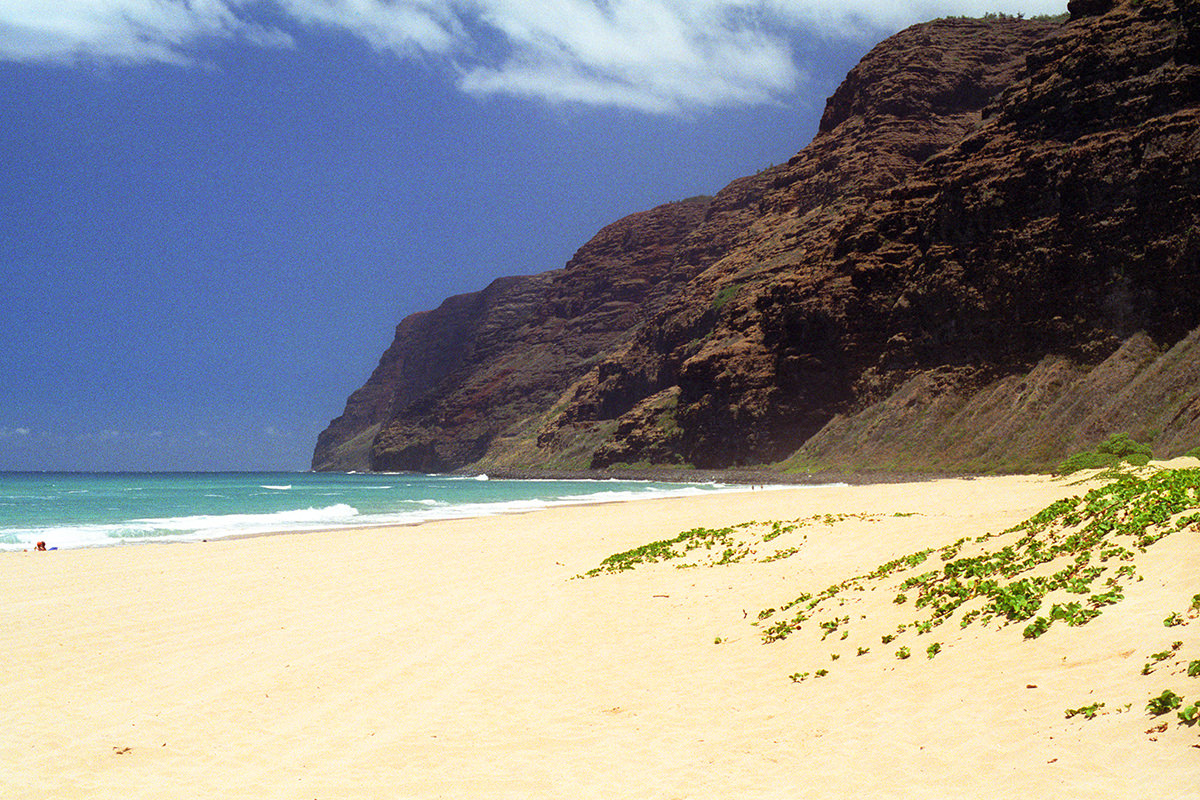 A photo of gorgeous Polihale Beach with pretty water and a looming cliff in the distance.