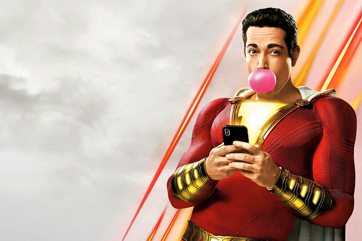 Shazam in his stupid suit looking at a stupid mobile phone while stupidly blowing a bubble with some gum.