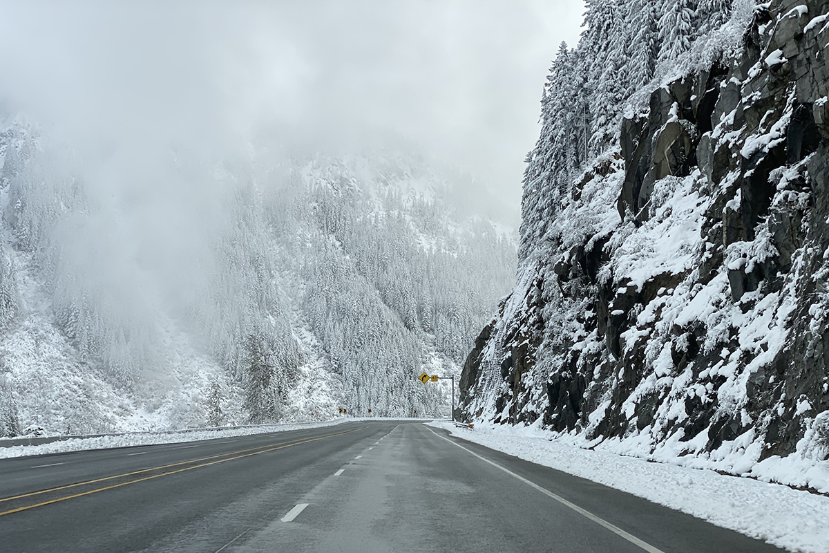 Driving through the mountains with snow-covered trees all around.