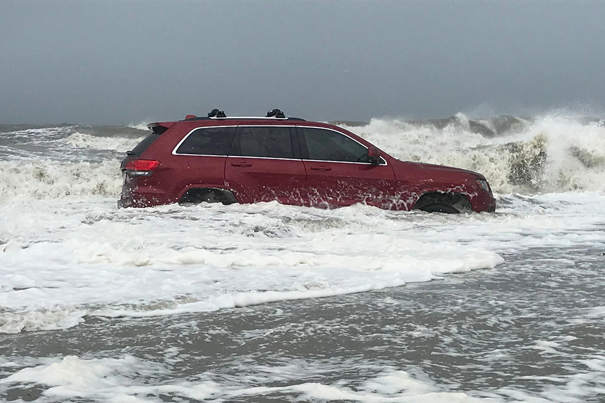 A photo of a red SUV stuck on the beach while waves crash around it.