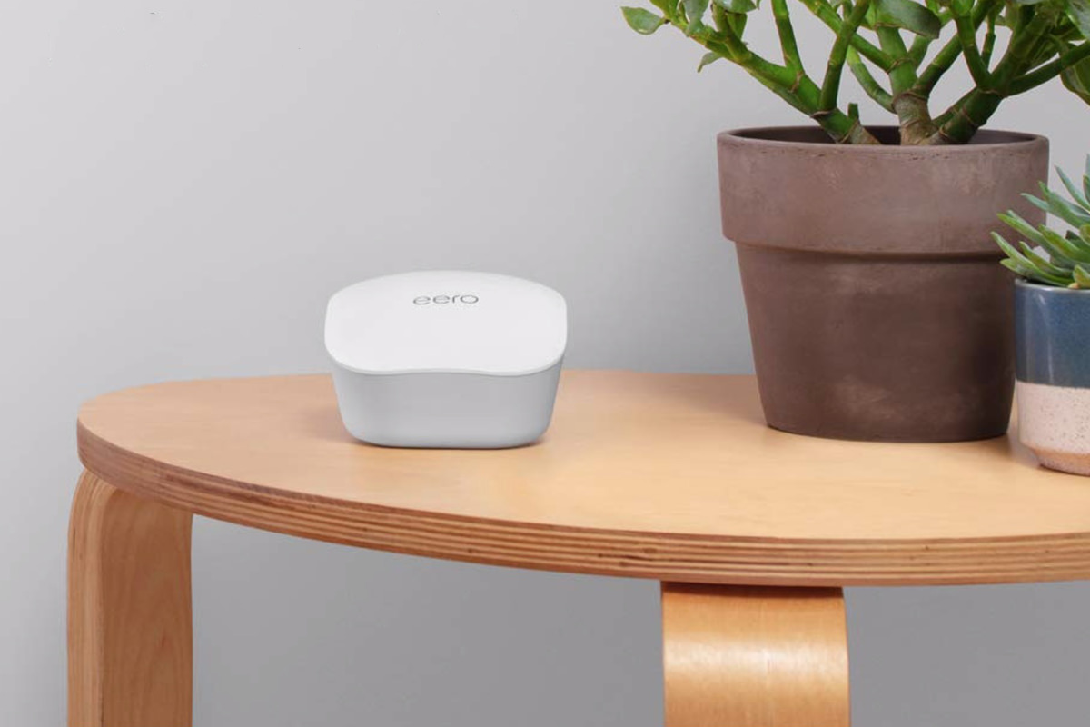 An eero mesh router pod sitting on a desk and looking like shit.