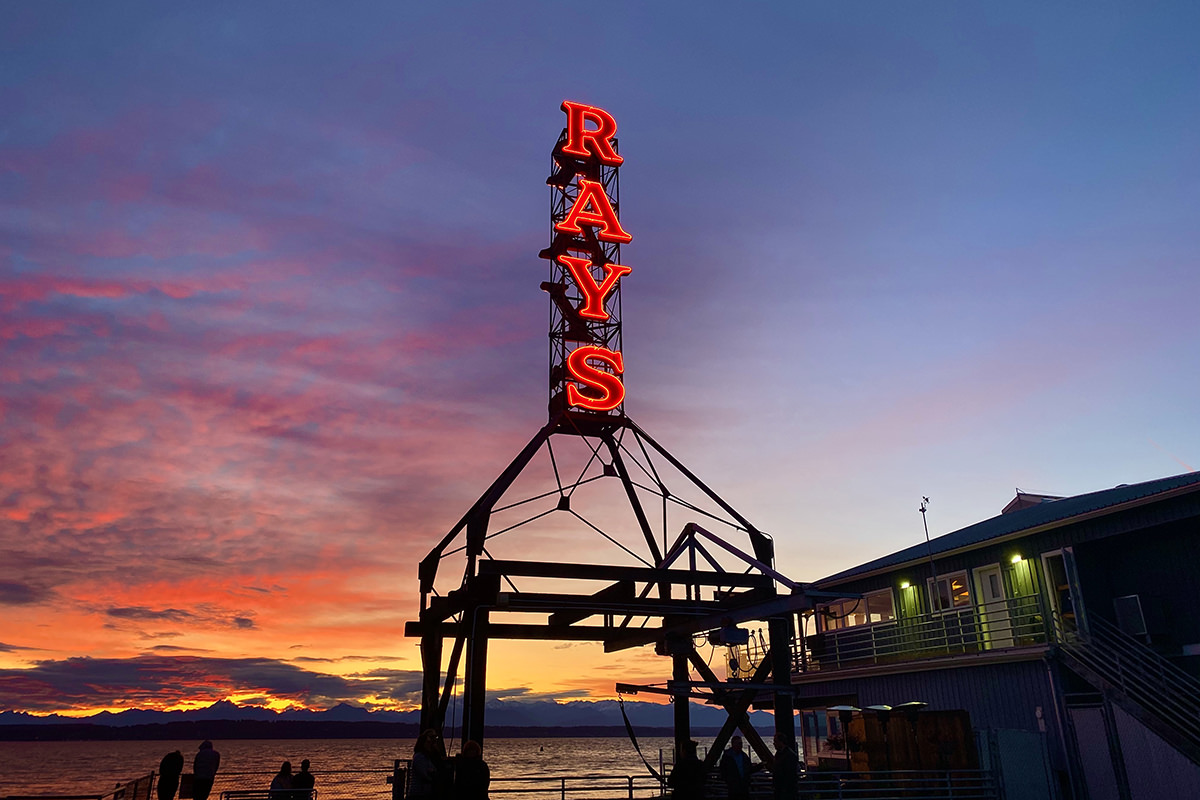 A beautiful shot of the Ray's Boathouse neon sign glowing while intense colors of sundown light up the sky behind it.