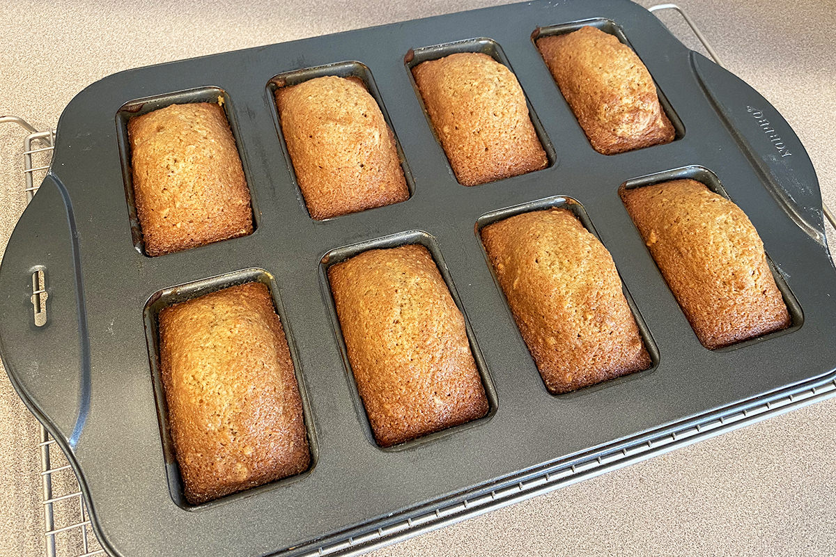 Cooked applesauce bread cooling in a tray with eight mini loaves stamped in it.