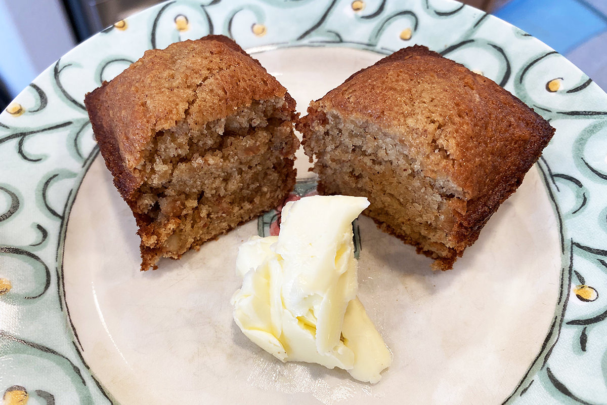 A mini loaf of applesauce bread on a plate with a massive pat of butter.